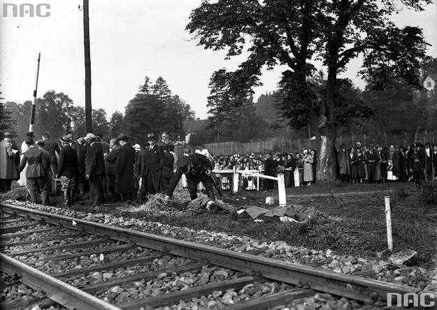 Zwłoki ofiar ułożone obok toru. Widoczny policjant z karabinem i tłum ludzi /Z archiwum Narodowego Archiwum Cyfrowego